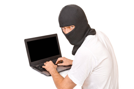 Man in black mask looking at camera with evil view and typing something photo