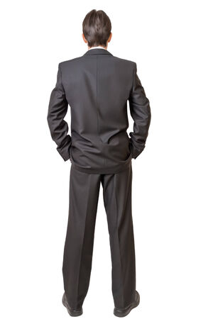 businessman standing: Backside of man in black suit keeping hands in pockets isolated on white background
