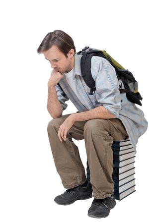 Male student with backpack sitting on the stack of books and thinks - isolated on white photo
