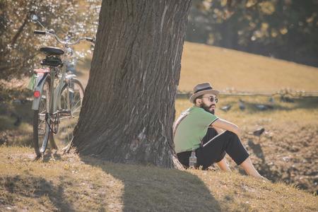 2015 년 9 월 10 일, 피터스 버그, 러시아 : 힙 스터 스타일을 입은 남자는 자전거로 공원에 도착하여 자연, 조류 및 맑은 날 배경에서 맥주를 마시고 마시