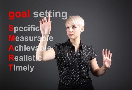 Goal setting concept - business woman touching screen photo