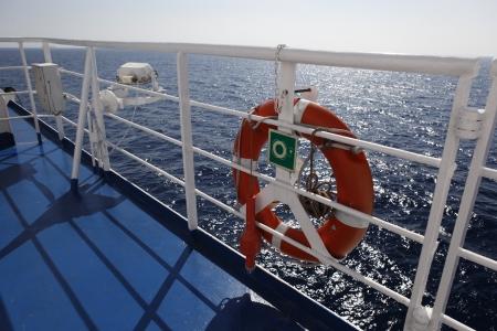 Bouée de sauvetage rouges en face de la mer bleue et le bateau blanc Banque d'images - 16077859