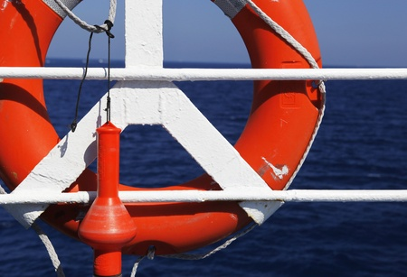 Red Life buoy in front of the blue sea and the white ship photo