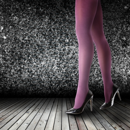 Womans Legs Wearing Pantyhose and High Heels in empty room photo