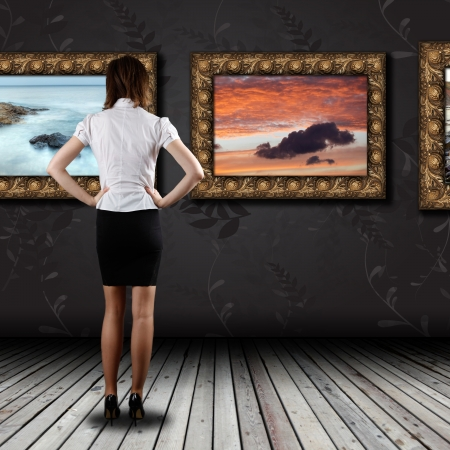art gallery: Woman standing in the gallery and watching art Stock Photo