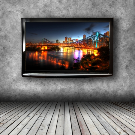 Plasma TV on the wall of the room with wooden floor photo