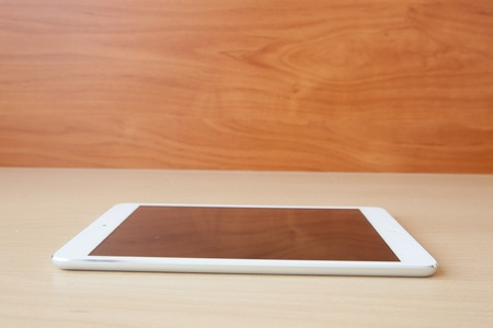 Tablet lying on the table with blank screen photo