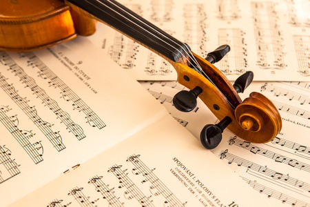 Old violin lying on the sheet of music, music concept photo