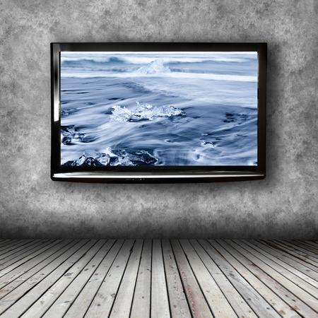 TV de plasma en la pared de la habitación con piso de madera Foto de archivo