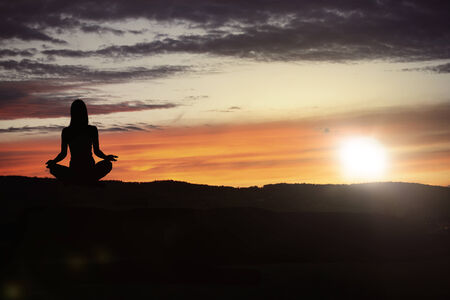 Yoga practicioner during the sunset meditation photo