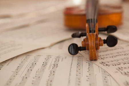 Old violin lying on the sheet of music, music concept Foto de archivo