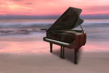 피아노는 외부 일몰 동안 해변에서 촬영
