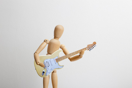 Wooden dummy posing with the electric guitar Stock Photo