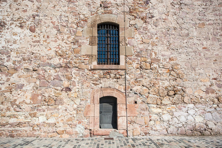 iron barred: Old wall  with jail window atfortress in Barcelona Stock Photo