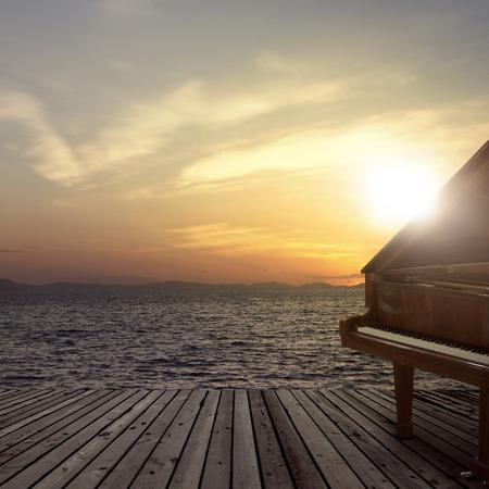 Klavier draußen am Meer bei Sonnenuntergang erschossen