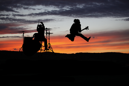 Band performing live during sunset at outside concert Stock Photo
