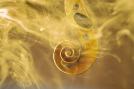Old violin head surrended with colored smoke and flames - music concept