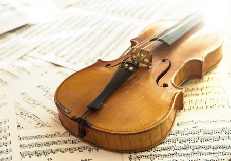 cellos: Old violin lying on the sheet of music, music concept Stock Photo