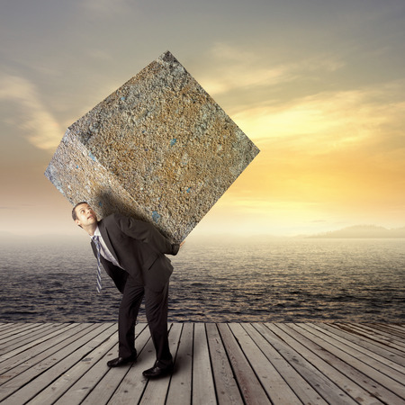 back ache: Businessman carrying heavy package - concept of tough career in the business