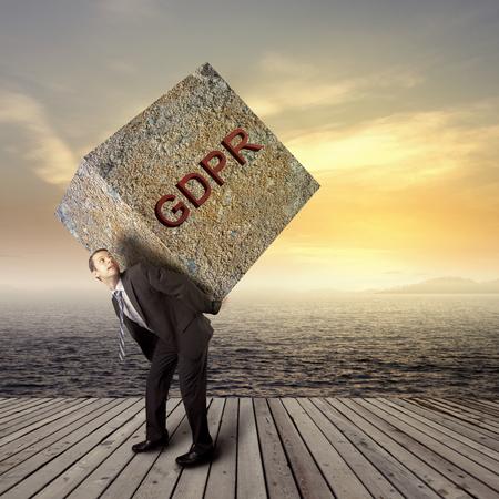重いパッケージ - GRPR のコンセプト - 一般的なデータ保護規制を運ぶビジネスマン 写真素材