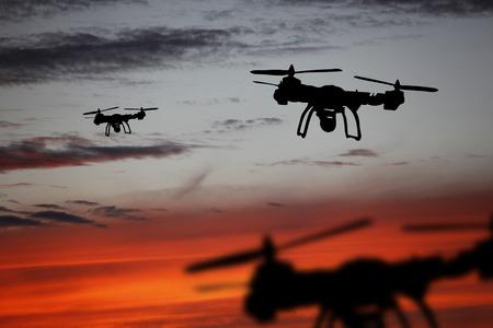 Conceito de inovação. Silhueta de drone voando no pôr do sol. Zangão pesado do elevador que fotografa no por do sol.
