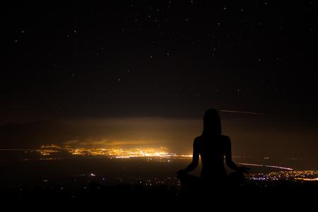 Yoga practicioner during the sunset meditation at mountains