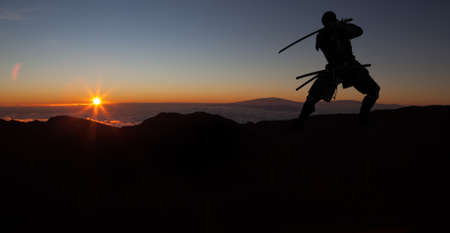 Silhouette of a Japanesesamurai with sword training and posing during sunset