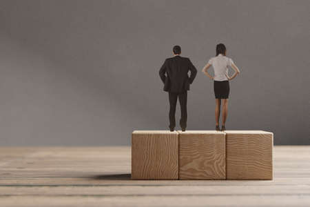 Miniature man and woman standing on the wooden blocks. The concept of the equal opportunities for genders.