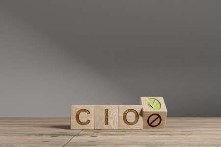 Wood cubes with acronym 'CIO' - 'Chief Information Officer' on a beautiful wooden table, studio background. Business concept with copy space.