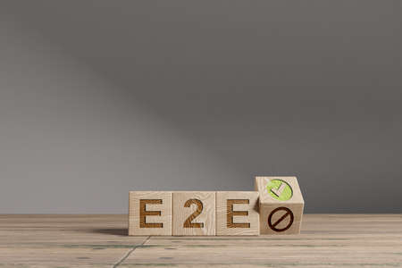 Wood cubes with acronym 'E2E' - 'End 2 End Processes' on a beautiful wooden table, studio background. Business concept with copy space.