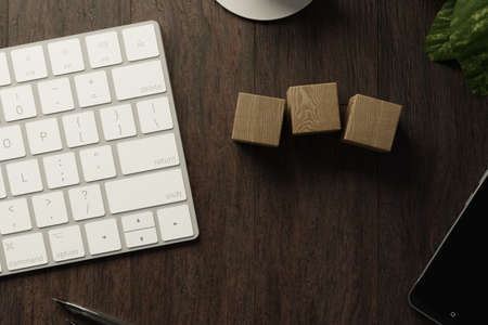 Work from home. desk office with keyboard, blank wooden cubes, coffee cup and pen on wood table. Flat lay top view