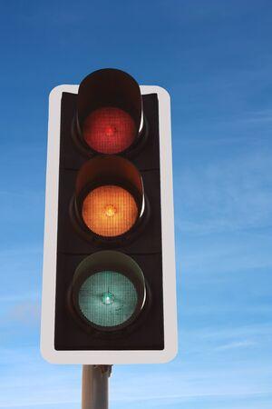 交通信号灯赤オレンジ色の青い空を背景に緑