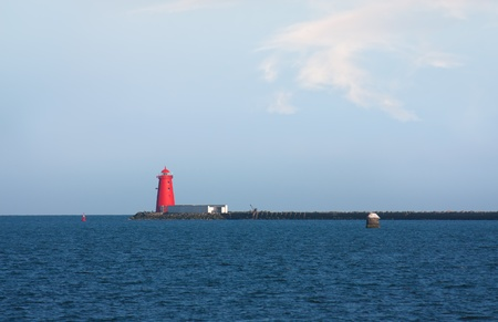 Red lighthouse and peer in a blue sea and some fluffy clouds Stock Photo - 12986637