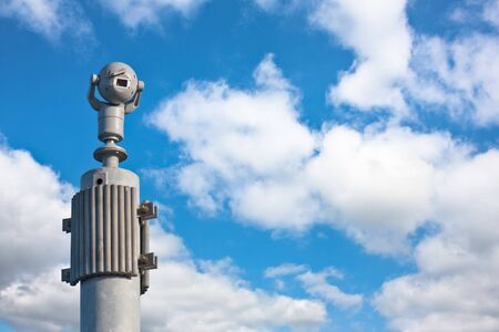sturdy: 360 round view security camera on a sturdy pole against a blue sky with clouds