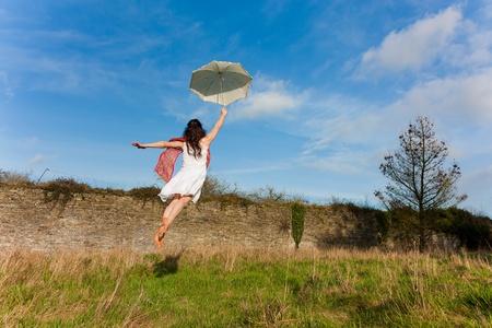 Chica volar con un paraguas