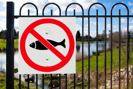 No fishing sign on fence with pond Stock Photo - 13448849
