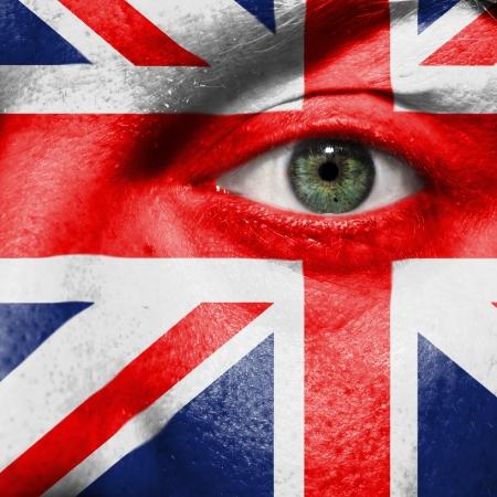英国のサポートを示すスポーツの試合で緑色の目と顔に描かれた旗
