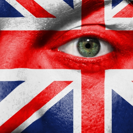 Flag painted on face with green eye to show UK support in sport matches Stock Photo