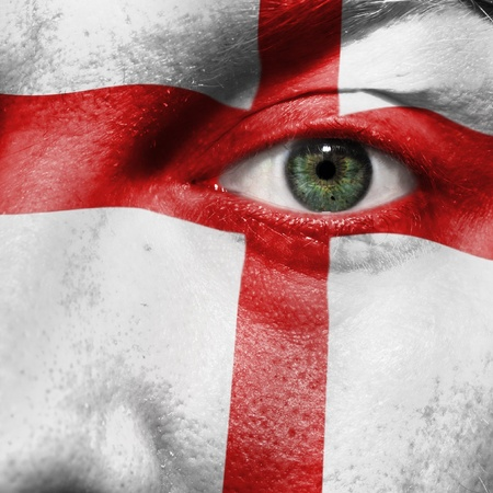 Flag painted on face with green eye to show England support in sport matches Stock Photo