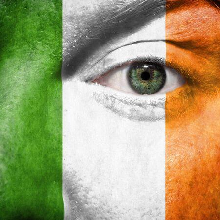 アイルランドのサポートを示すスポーツの試合で緑色の目と顔に描かれた旗