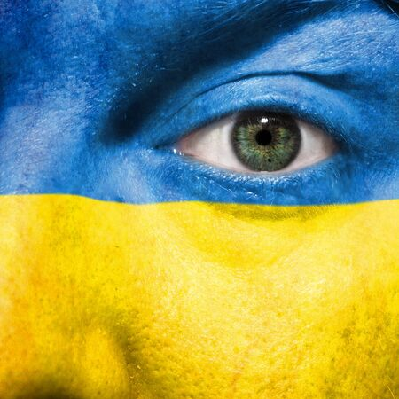 Flag painted on face with green eye to show Ukraine support in sport matches Stock Photo