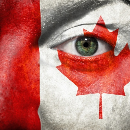 Flag painted on face with green eye to show Canada support in sport matches Stock Photo