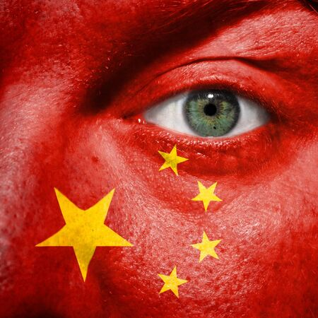 Flag painted on face with green eye to show China support in sport matches photo