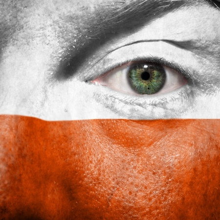 Flag painted on face with green eye to show Poland support in sport matches Stock Photo