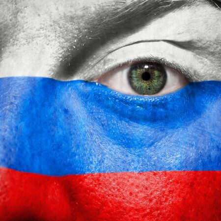 Flag painted on face with green eye to show Russia support in sport matches Stock Photo