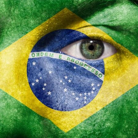 ブラジルのサポートを示すスポーツの試合で緑色の目と顔に描かれた旗