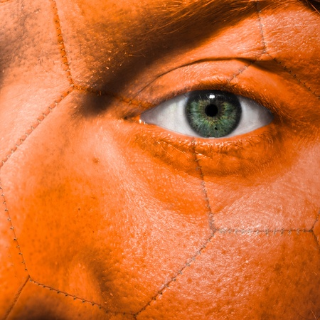 Football painted on orange face with green eye to show support in sport matches photo