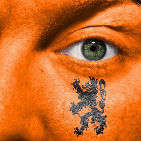 オランダのサポートを示すスポーツの試合で緑色の目とオレンジ色の顔に描かれたオランダのライオン 写真素材