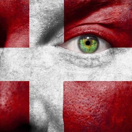 Flag painted on face with green eye to show Denmark support Stock Photo