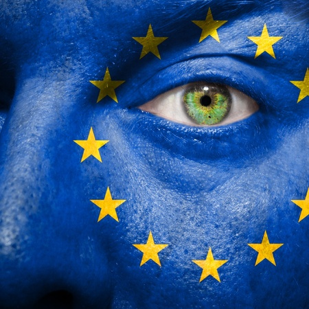 Flag painted on face with green eye to show Europe support photo